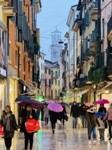 The Via Mazzini - you can see the buildings on either side of the street and shoppers are walking down with their umbrellas up