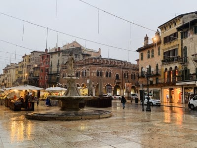 The Piazza delle Erbe - you can see some market stalls and a fountain in the middle.  It is wet from rain and the light is dim