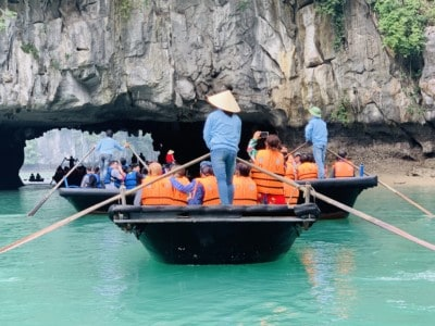 A view of some bamboo boats steering under a small archway on Halong Bay.  The boat is steered from the back by a sailor.