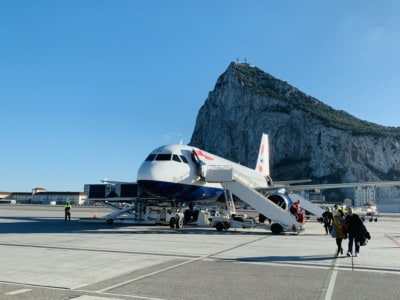 A picture of a British Airways plane on the runway in Gibraltar.  You can uniquely walk across this runway to your hotel