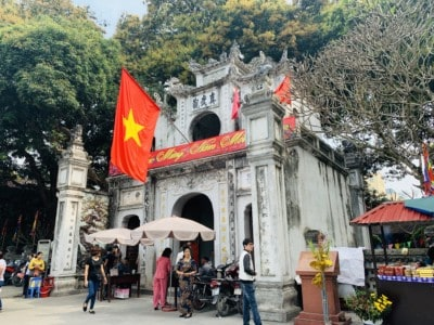 The Quan Thanh temple.  Yu can see the entrance with a flag outside.  There are stalls and people outside this.