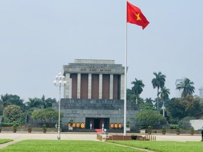 A view of the Ho Chi Minh mausoleum.  This is a square building with white pillars and the name Ho Chi Minh above them.  You can see Vietnamese flag flying the foreground