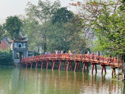 The pretty red bridge that you walk across to reach the Ngoc Son Temple.  There are people walking across to this and you can see a temple gateway on the left.  Trees surround the bridge and temple.