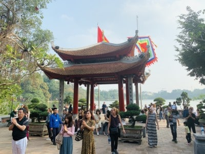 One of the temples in the Ngoc Son Temple.  There are lots of tourists visiting this and you can see the lake in background.