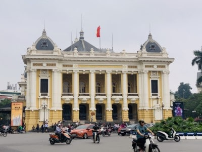 Hanoi's opera house.  This is an ornate yellow and white building with a flag on the top.  You can see cars and moped driving outside the opera house.