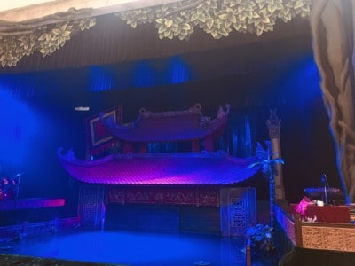 The stage at the water puppet show we saw.  The stage is bathed in blue light here and you can see a temple as part of scenery, as well as the curtains by the stage.