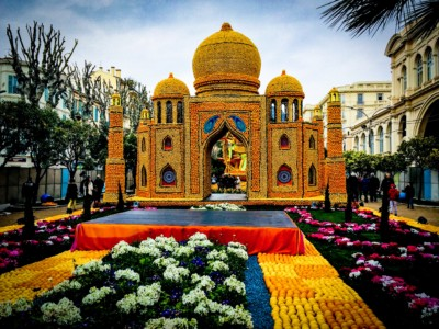 A Taj Mahal made of oranges and lemons.  It has a walkway of citrus fruits and flowers leading up to it and a building on the right