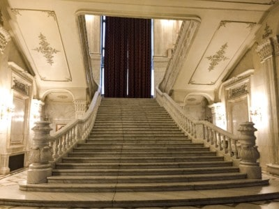 An ornate marble staircase in the People's Palace.  This is white with red curtains at the top