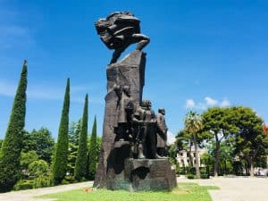 An image of Albania's Monument of Independence in Vlore.  This is a tall striking monument with figures around it.  You can see trees on either side of the avenue on which it stands.