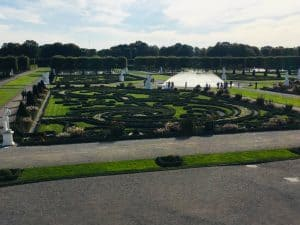 A view over part of the Grosser Garten in the Royal Gardens of Herrenhausen.  You can see a swirling geometric patterns cut into the lawn and a small fountain