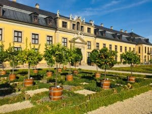 The orangery in the Royal Gardens of Herrenhausen.  You can see small orange trees outside a long yellow building.