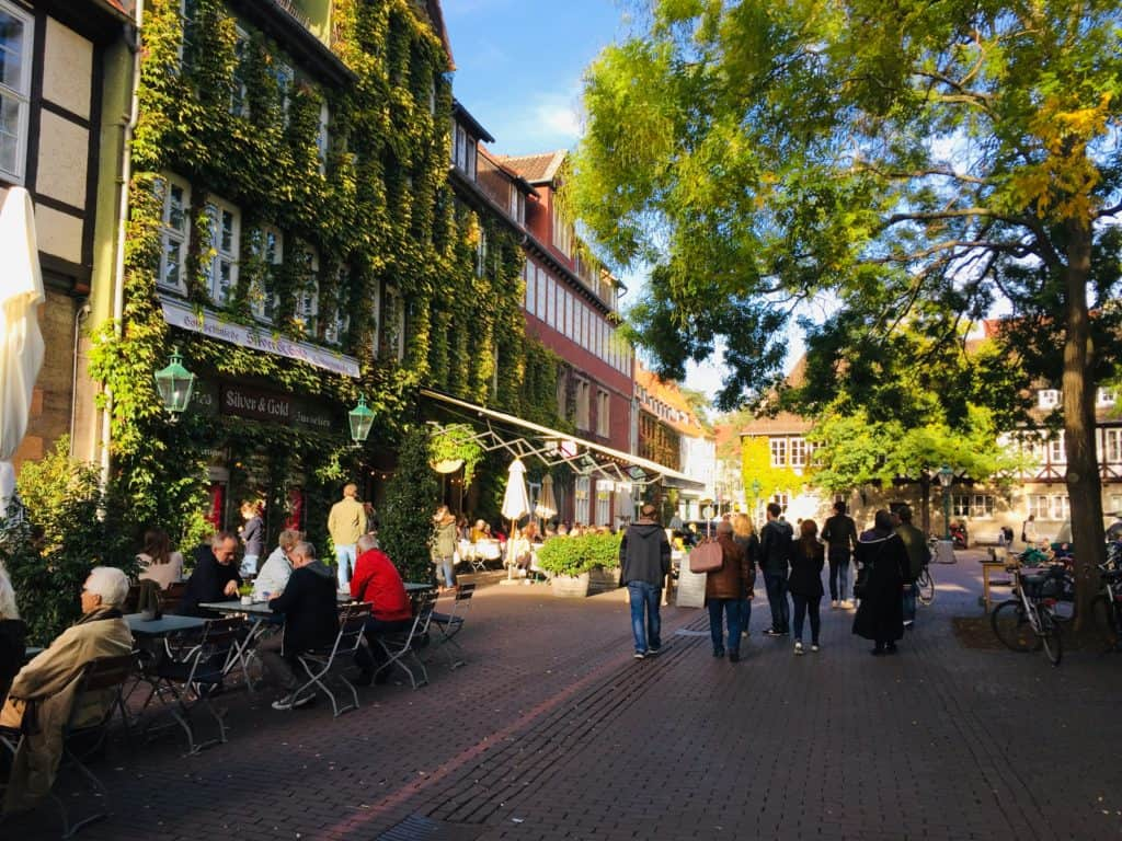 Ballhofplatz Square with its restaurants with outdoor seating.  It's quite leafy with a large tree in the centre and one building covered in green vines.  You can see see people wandering around.