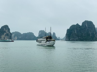 A view of part of Halong Bay.  You see the limestone islands and a boat sailing between them.