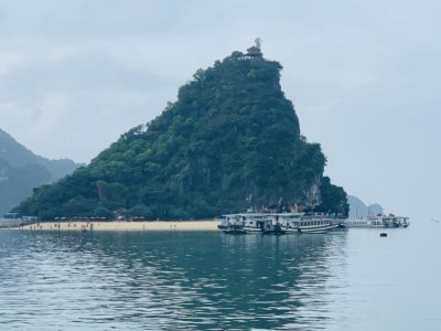 A view of Ti Top island that you can visit on a 1 day Halong Bay tour.  This is a large triangular rock jutting out of the water.  It's covered in vegetation with a sandy beach at the front.  There are boats sailing around it