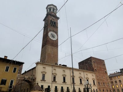 The Torre dei Lamberti. It is brown and slim, with a clock on the front.