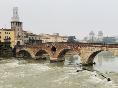 A picture of the Ponte Pietra bridge.  This has brown and yellow bricks and is arched  You can see houses in the background and a tower, as well as the duomo in the distance