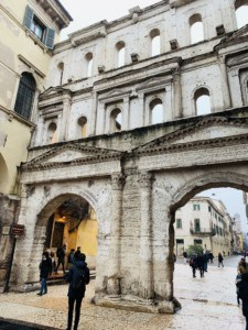 A picture of La Porta Borsari, a city gate.  This has arches to walk through into the street.  It is white