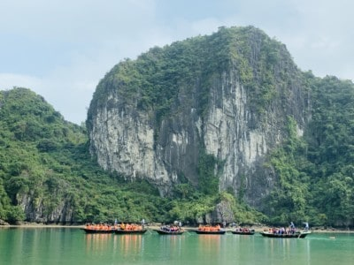 A view of another part of Halong Bay that you may see on a Halong Bay day cruise.  There's a massive limestone rock in the background and lots of bamboo boats sailing on the water