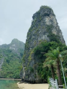 A picture of a massive limestone rock on a beach when you pull up to see Sung Sot cave as part of your Halong Bay 1 day tour