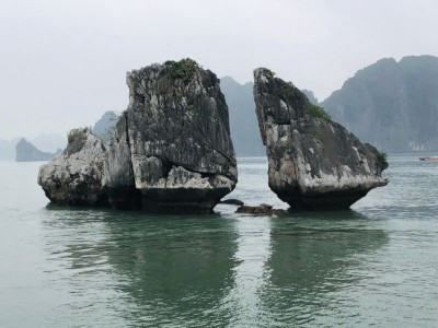 """The """"two chickens kissing"""" set of rocks that you see on Halong Bay day cruise.  These are two triangular shaped rocks close together and on their side."""