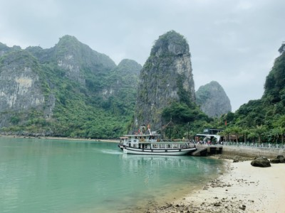A view of the sandy bay when you pull up to see Sung Sot cave as part of your 1 day Halong Bay tour.  You can see lots of limestone rocks here and a cruise boat moored in the bay.