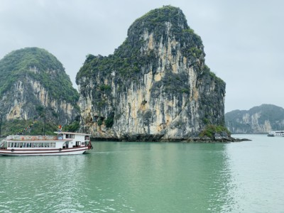 A view of part of Halong Bay that you can see on a on a Halong Bay day cruise.  You see the limestone islands and a boat sailing between them.