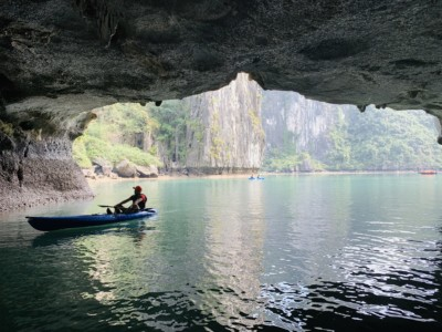 A view of a lone canoeist sailing underneath a low archway on Halong Bay