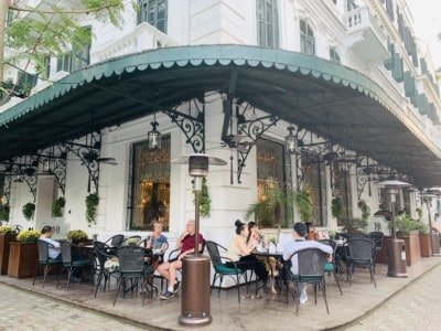 Outside the Sofitel Legend Metropole Hotel.  People are sitting drinking at tables outside the hotel.  There is a green awning here.