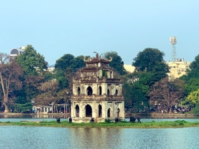 A picture of the Turtle Tower in Hoan Kiem Lake.  This a small, almost square temple with arches throughout it.  You can see trees behind it.