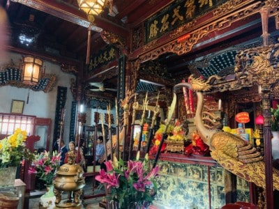 The inside of one of the Quan Thanh temple.  You see pots, colourful flowers, lanterns hanging from the ceiling and ornate decorative details.