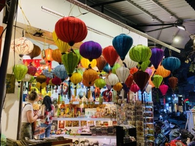 Some colourful paper lanterns hanging in a shop on the side of the street in Hanoi's old town