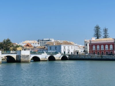 Tavira's Roman bridge with the river in the front and colourful buildings behind