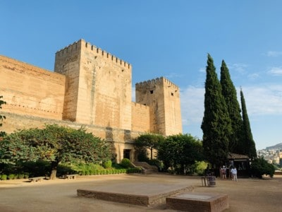 Picture of the outside of part of the Alcazaba that you can see when visiting the Alhambra.  There are trees and an open courtyard in front