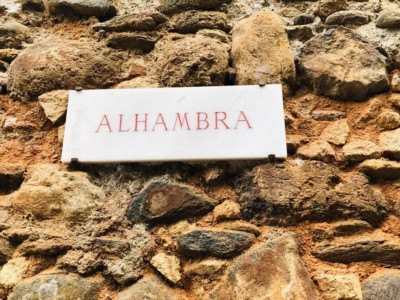 Alhambra name plate on the wall with the red brick beneath