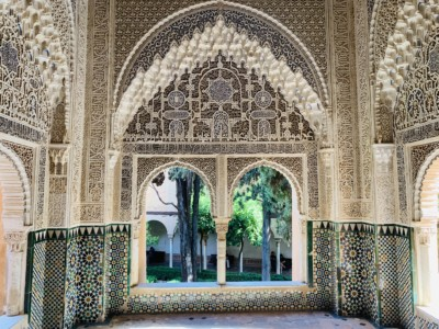 A side alcove in the Nasrid Palace that you can see when visiting the Alhambra.  This has an arch and windows looking out onto a leafy outside area and beautiful ornate Moorish design