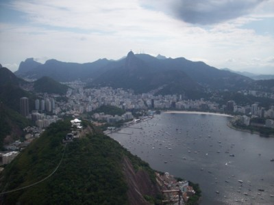 A view from Sugarloaf Mountain in Rio - looking down into the bay with a beach and high rise buildings
