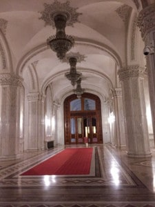 A walkway in the Palace that you can see when visiting this Bucharest attraction.  This is white and marble and with a red carpet on the floor and chandeliers hanging from the ceiling