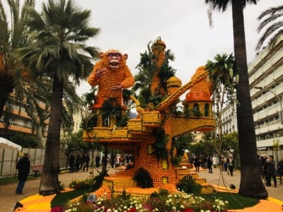 "A ""monument"" of oranges and lemon.  This is a monkey on top of a childlike house.  It is surrounded by palms trees"
