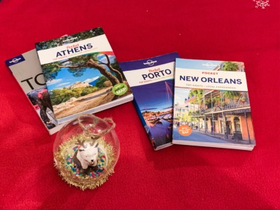A picture of some Lonely Planet pocket guidebooks with a Christmas bauble in front.  There is Tokyo, Athens, Porto and New Orleans.  These would be great gifts for someone going travelling for the weekend or a short break