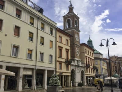 A picture of a street in Rimini with a pretty clock tower