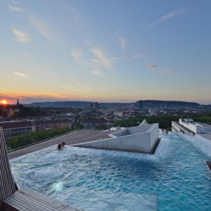 The rooftop pool of the spa.  You can see two people in the pool and there are views out across Zurich city