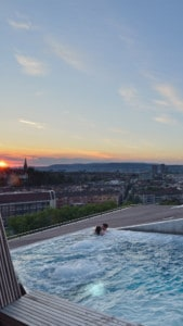 Image of the rooftop pool in the spa - you can see two people in the pool and there are views out across Zurich