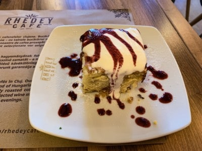 A picture of a portion of Vargebeles cake.  This is a square song type cake with cream on the top and a fruit compote drizzled over and around it