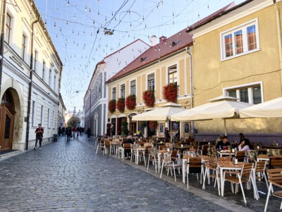 Cluj old town.  You can see a pretty restaurants along one side with tables outside and flowers from the windows