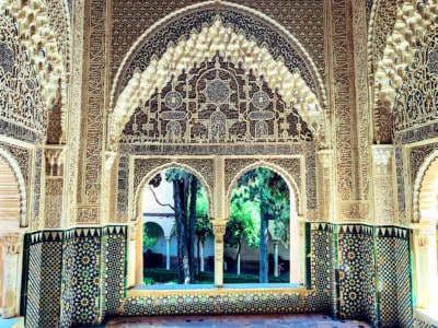 The intricate designs inside the Nasrid Palaces.  You can see an ornate white arch with windows and a green Moorish design below