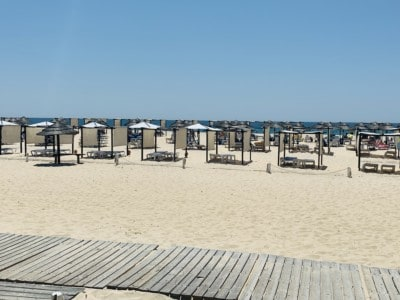 The beach at the Ilha de Tavira.  You can see white sand with a boardwalk in front and sun beds and coverings