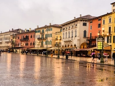Piazza Bra in Verona.  You can see the colourful buildings with their awnings.  The ground is wet from rain.