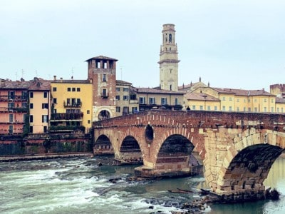 The Ponte Pietra bridge in Verona.  This has arches and there are buildings and a tower in the background