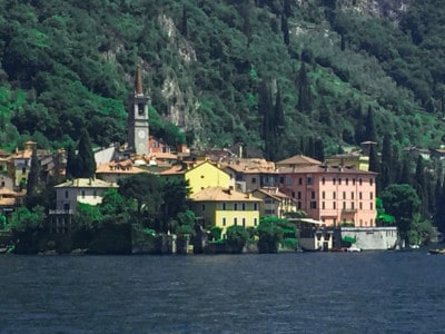 A view of Bellagio from the lake, one of the towns on Lake Como.  You can see the colourful houses and the steeple of a church.  You can see the vegetation on the hill behind.