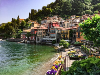 The view of Varenna, one of the small towns on Lake Como.  You can see a small bay, the colourful houses, the trees behind and some canoes on the shoreline.